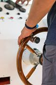 Strong Male Captains Hand On The Helm Handle Of A Yacht Ship. Man Steers A Sea River Vessel Boat poster