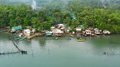 Fishing Village With Wooden Houses Standing On Stilts In The Sea From Above. Houses Community Standi poster