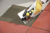 stock photo of mortar-joint  - Worker With Notched Trowel Install Red Tiles With Tile Adhesive - JPG