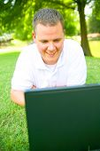 Happy Young Man Smiling To Laptop