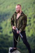 Man Brutal Poacher With Weapon Natural Landscape Background. Hunter Poacher Looking For Victim. Hunt poster