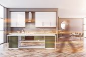 Blurry Man Walking In Gray Kitchen With Green Countertops And Island, White Cupboards And Dining Tab poster