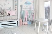 Clothes For Little Child Hung In Children Room. Rack With Hangers With Baby Clothes. Children Cloth  poster