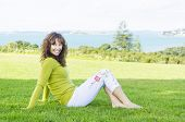 happy smiling mature woman sitting on grass