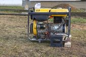 Close-up. Street Lighting. A Gasoline-powered Generator That Produces Current. A Car Battery Is Conn poster