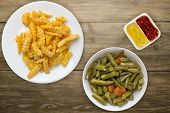 French Fries On A White Plate In The Brown Wooden Background. French Fries With Vegetable Salad Fast poster