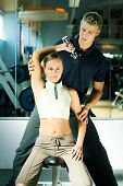 image of personal trainer  - Woman lifting dumb - JPG