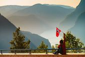 Tourist Woman With Norwegian Flag Enjoying Fjord Aurlandsfjord View From Stegastein Viewing Point. N poster