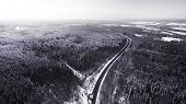 Road in the winter forest covered snow. Aerial View. Russia, Siberia, Altai region poster