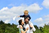 Cute Boy With Parents Playing Outdoor. Enjoy. Childhood. Father Giving Son Ride On Back And Hug Wife poster