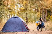 Young Woman In Warm Sweater And Black Hat Resting With Guitar Near Camping Tent In Wilderness Forest poster