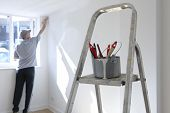 stock photo of tin man  - man decorating a room with ladder and paint pot in foreground - JPG