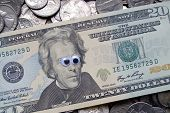 stock photo of googly-eyes  - A twenty dollar bill on a bed of coins - JPG