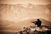 picture of golan-heights  - A figure of a Shooting Man with mountains as abackdrop - JPG