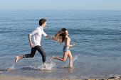 stock photo of chase  - Couple chasing and running on the beach shore splashing water - JPG