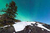Northern Lights Aurora borealis over snowy rocks
