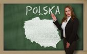 Teacher Showing Map Of Polska On Blackboard