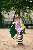 Small Thoughtful Beauty Girl On Swing.