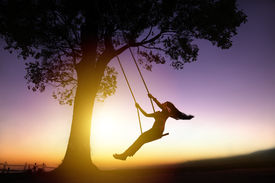 image of swing  - silhouette of happy young woman on a swing with sunset background - JPG