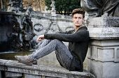 Handsome Young Man Outdoors, Sitting On Old Stone Balusters