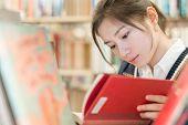 Student Reading A Book On Bookshelf