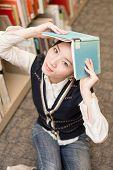 Girl Holding A Book Over Head Near Bookshelf