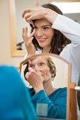 Female eyecare doctor teaching senior woman to insert contact lens in optician store