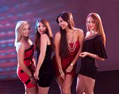stock photo of vivacious  - Group of glamorous young women in evening attire dancing together at a nightclub or disco - JPG
