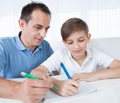 Portrait Of Father And Son Doing Homework