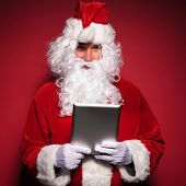 santa claus is holding and reading on a tablet pad computer on red background