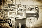 Vintage representation of fishing boats in Peggy's Cove, Nova Scotia, Canada. Gritty look with sepia