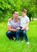 Father keeps son on the knee in the park. Concept of happy family relations and carefree leisure time