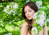 picture of nearly nude  - Portrait of attractive woman near the flowered tree in the park - JPG