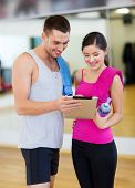 fitness, sport, training, gym, technology and lifestyle concept - two smiling people with tablet pc
