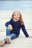 Portrait of 4 years old girl walking on berth near sea in the city, still life photo