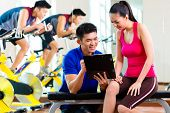 Asian Chinese Woman and personal fitness trainer in gym discussing training schedule and goals for w