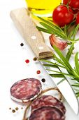Close-up traditional sliced meat sausage salami with knife and vegetables