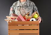 Closeup of a soldier in fatigues holding a wooden box full of toys and sports equipment for a holida