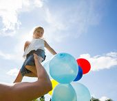 Mother lifting daughter holding colorful helium balloons against cloudy sky