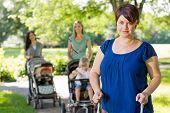 Portrait of mid adult mother holding baby stroller at park with friends in background