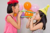 Side view of two young girls blowing noisemakers at a birthday party
