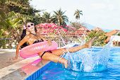 image of flesh air  - Young woman in bikini with pink inner tube having fun near pool at tropical resort in summer day - JPG