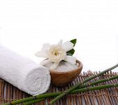 Spa sitting with towel and, gardenia ,salt in bowl on mat