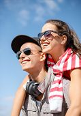 summer holidays, relationships and teenage concept - smiling teenagers in sunglasses having fun outs