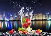 Summer drinks splashing, with blur night modern city on background