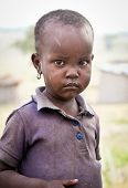 AFRICA, TANZANIA-FEBRUARY 9, 2014: Portrait on an African girl of Masai  tribe village looking to th
