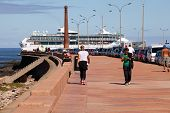 MONTEVIDEO, URUGUAY - MAR 20 2014 : A cruise ship passes walkers on the Rambla as it approaches port