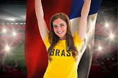 Pretty football fan in brasil t-shirt holding chile flag against vast football stadium with fans in