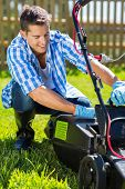 young man emptying lawnmower grass catcher after mowing the lawn