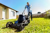 low angle view of young man mowing lawn at home